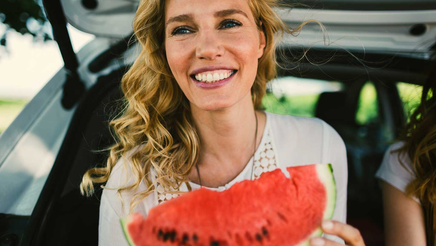 Happy woman eating watermelon