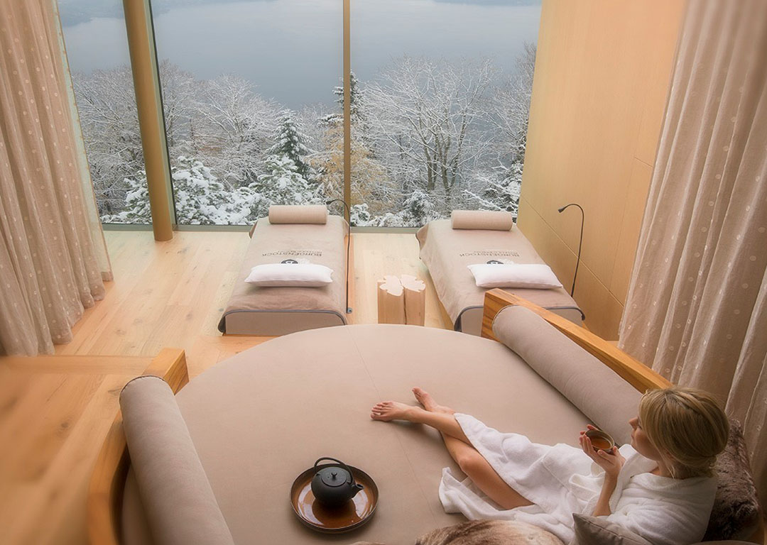 woman relaxing on round chair looking at Alpine scenery at Buergenstock Alpine Spa