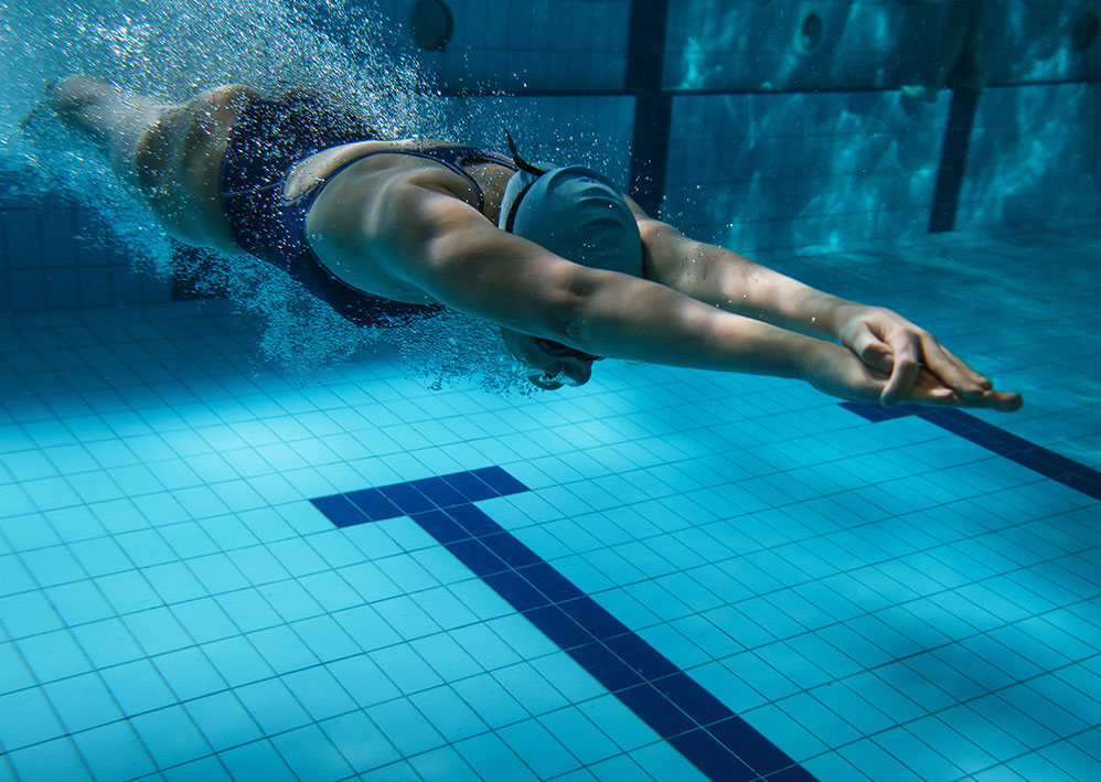 Person swimming underwater in pool