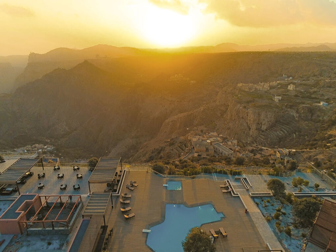 aerial view of hotel with sun setting over distant mountains