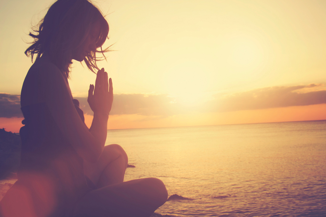 a woman meditates while the sun sets