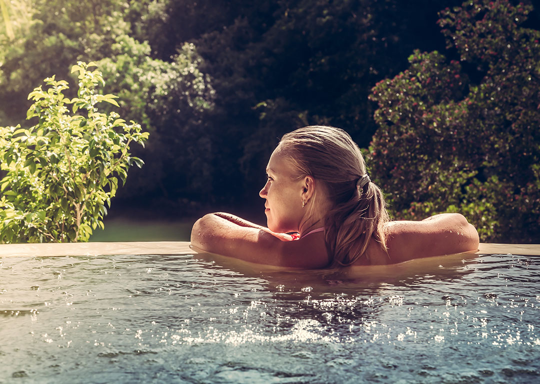 Woman in outdoor pool overlooking trees